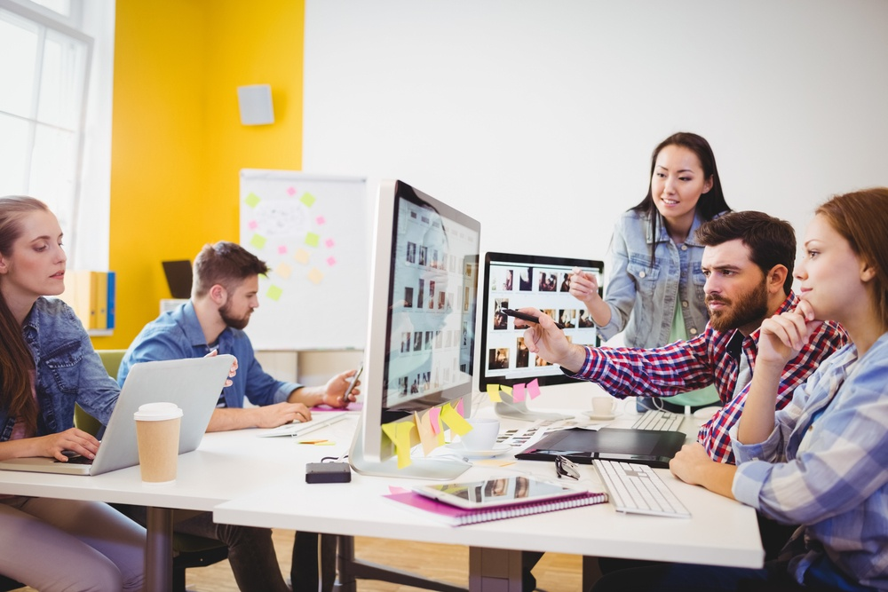 Businessman showing computer screen to coworkers in creative office.jpeg