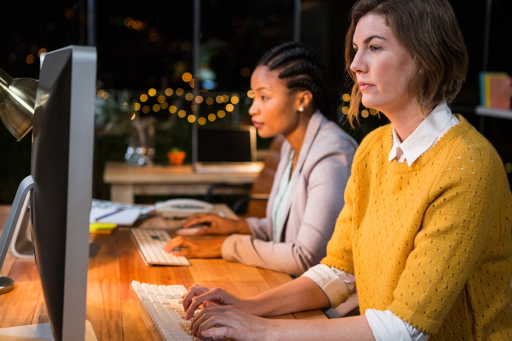 Businesswomen working on computer at their desk in the office.jpeg