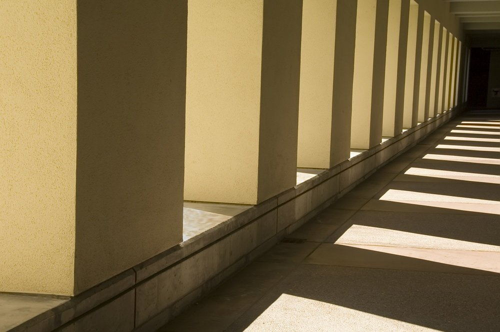 Interplay of sunlight and shadow along passageway outside university building