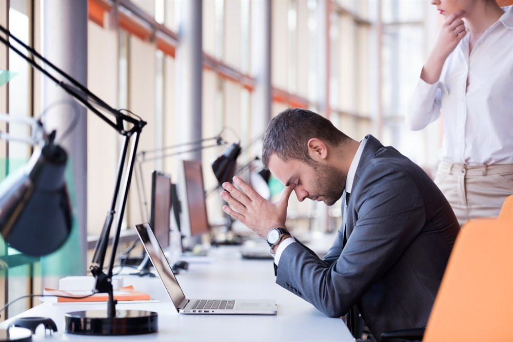 frustrated young business man working on laptop computer at office-1.jpeg